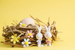 Close up. Easter card. Brown eggs in a nest of straw. Two bunnies in the foreground. The decor of the felt flowers. Yellow. Close up, macro. Easter card. Brown stock images