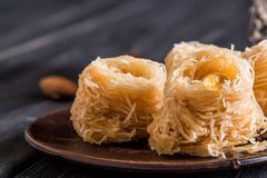 Close up, macro. Eastern sweets on an old clay saucer. Turkish traditional Baklava bird`s nest. Dark wooden background royalty free stock image