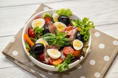 Close up. French cuisine. Traditional niçoise nicoise salad in a white plate on a polka dot napkin. White background