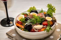 Close up, macro. French dinner served with red wine. Traditional niçoise nicoise salad in a white plate on a polka dot napkin