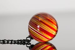 Colorful marble, Crystal ball, glass ball, marble mirror reflection. Close up macro glass ball, red and yellow colored crystal marble, stripes ball with black Royalty Free Stock Photo