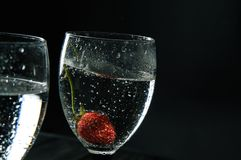 Close up, macro. The glass is filled with sizzling wine. At the bottom of the berry is covered with bubbles. Copy space