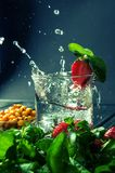 Close up, macro. A glass topped with a drink, decorated with strawberries and mint. One berry falls into a liquid with a splash,. The droplets fly apart. Blue stock photography