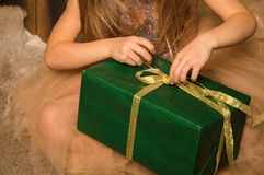 Close up, macro. Hands of a little girl in a golden dress unpack a gift. The box is wrapped in green paper. Christmas concept