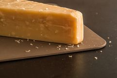 Italian cuisine. A chunk of parmesan cheese on a brown board. Black background.