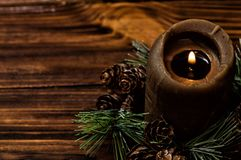A lit brown candle is decorated with a spruce branch with small cones. Brown wooden boards on the background.