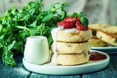 Close up, macro. Lush cheese pancakes, poured with cream and decorated with strawberries and mint. Close up, macro. Traditional rustic breakfast. Lush cheese royalty free stock images
