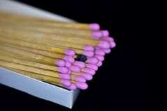 Close-up macro of pink wood stick matches in a box. Matches stacked in a white box with pink heads and one used on Match wooden matchsticks Royalty Free Stock Images