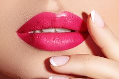 Close-up macro shot of female mouth. Glamour red lips Makeup with sensuality gesture. Magenta gloss lipstick. Full lips stock photo