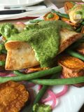 Close up macro shot of seafood dish - fish with pesto sauce and vegetables Royalty Free Stock Images