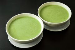 Close up. Two round white plate filled with green broccoli cream soup. Black background. Copy space stock images