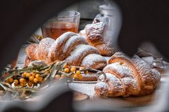 Close up. Valentine`s Day. Romantic breakfast with french croissants and hot tea. View through a carved wooden folding screen stock photo