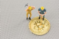 Close up macro view of miners figurine on bitcoin stock photo