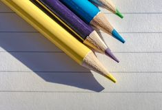 Coloured pencils seen on writing paper, seen within a classroom. royalty free stock photography