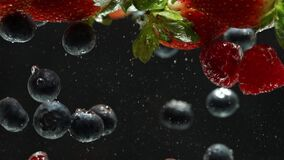 Close up macro view of raspberries, strawberries and blueberries falling into water.