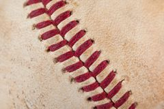 Close up macro view of red stitched seams of an worn baseball