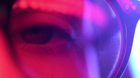 Close up macro woman blue eye in glases opening beautiful iris natural human in neon light. beauty healthy eyesight