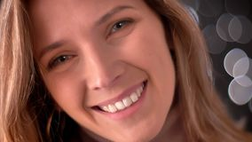 Close-up macroportret van gelukkig overweldigend Kaukasisch vrouwelijk gezicht die recht camera en het glimlachen bekijken stock footage