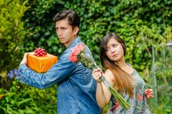 Close up of mad woman holding flowers and mad man holding a gift back to back ignoring each other, friend zone concept. Close up of mad women holding flowers and Stock Photos
