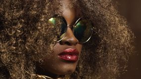 Close-up of magic golden african american female model in massive sunglasses with bright glitter makeup, glossy golden. Hairstyle and big red lips posing on the stock video