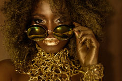 Close-up of magic golden african american female model in massive sunglasses with bright glitter makeup, glossy
