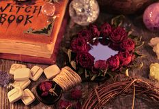 Close up with magic mirror, witch book and runes on the table. Occult, esoteric and divination still life stock images
