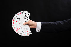 Close up of magician hand holding playing cards. Magic, performance, circus, gambling, casino, poker, show concept - close up of magician hand holding playing Royalty Free Stock Images