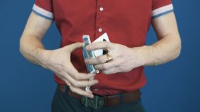 Close up magician in red shirt shuffle playing cards, show Queen of Spades stock video