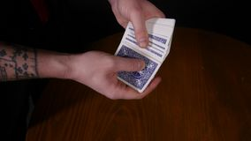 Close-up of a magician`s hands performing card tricks, making fan out cards on black background.  stock video footage