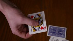 Close-up of a magician`s hands performing card tricks, making fan out cards on black background.  stock footage