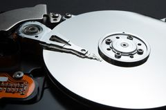 A close-up of a magnetic disk and a reading head on a black background. Restore personal data of users on the hard disk stock photography
