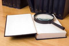 Close-up of magnifying glass on a book. Close-up of magnifying glass on an opened book with books on background royalty free stock photos