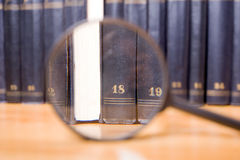 Close-up of magnifying glass with books. On background stock image
