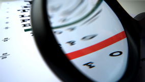Close up of a magnifying glass falling on an eye test Royalty Free Stock Photos