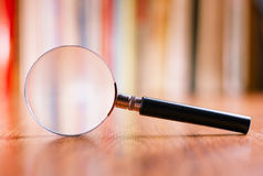 Close up Magnifying Glass Leaning on Wooden Table Royalty Free Stock Photos
