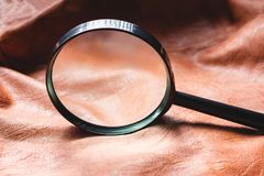 Close up of magnifying glass with leather background. Searching concept.  royalty free stock photo