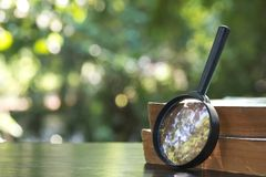 Close up of magnifying glass with old books on the wooden table royalty free stock image