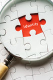 Close up Magnifying glass searching missing puzzle peace identity stock photo