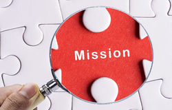 Close up Magnifying glass searching missing puzzle peace Mission Royalty Free Stock Photo