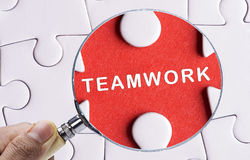Close up Magnifying glass searching missing puzzle peace Teamwork Royalty Free Stock Images