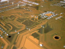 Close-up of a mainboard. Close-up of a brown mainboard with cpu in background Royalty Free Stock Image