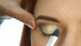 Close-up make-up artist hand, applying eyeshadow to woman`s eye using brush. slow motion. Close-up make-up artist hand, applying eyeshadow to woman`s eye using stock footage