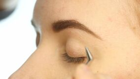 Close-up make-up artist hand, applying eyeshadow to woman`s eye using brush. 4K. Close-up make-up artist hand, applying eyeshadow to woman`s eye using brush stock video footage