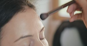 Close up of make up artist working with model face stock video footage