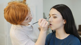 Close-up of a make-up artist applying make-up to the eyelash stock video