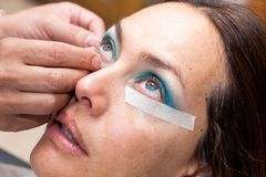 Make up artist using masking tape to create cat eyes Stock Images