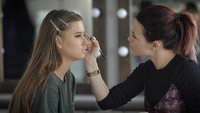 Close up of make-up process at beauty shop. Young visagiste is applying eyeshadow on model`s face using brush. Woman is stock footage