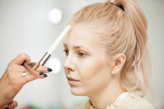 Close up of makeup trainer explayining something on the model Royalty Free Stock Images