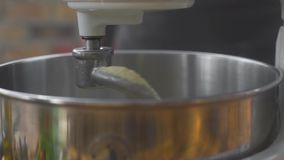 Close up making dough in kitchen mixer. Kitchen kneader machine mixing dough in bakery. Preparation ingredients for