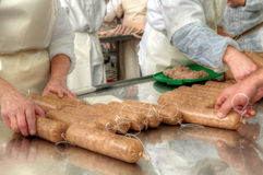 Close-up making sausages automatic process. Meat plant traditional sausage during the preparation Royalty Free Stock Photo